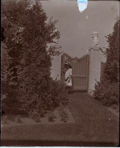 Child standing at the garden gate of the Saltonstall House, Milton, Mass.
