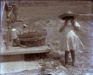 Child drinking from a cup by a water pump, Mashpee, Mass.