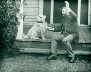 Man seated on a porch playing with a dog, location unknown, 1880s