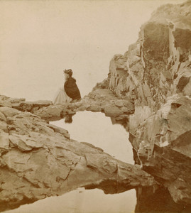 Stereograph of a woman seated on a rock, Crystal Pool, Bar Harbor, Maine, undated