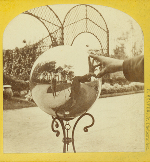 Stereograph of the photographer's reflection in a gazing ball, Ridge Hill Farms, Wellesley, Mass., undated