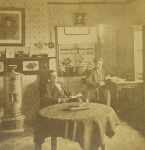Stereograph of two men sitting in a room, location unknown, undated