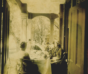 Half-length group portrait of the Bowen Family, seated, at tea, location unknown, undated