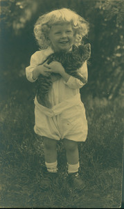 Full-length portrait of a child, standing, facing front, holding a kitten, location unknown, undated