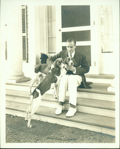 Portrait of Winston Churchill, seated on steps, facing front, with two hound dogs, Cornish, New Hampshire, undated