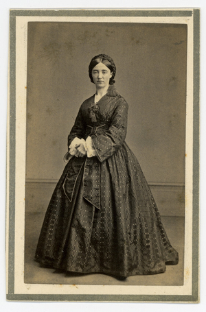 Full-length portrait of Edna Dean Proctor, governess, standing, facing front, location unknown