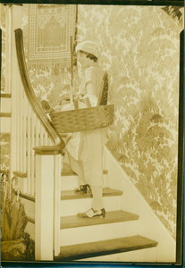 Woman with basket of cleaning supplies, undated
