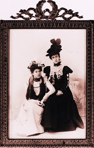 Full-length double portrait of two women, seated, facing front, location unknown