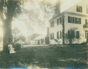 Portrait of Kate Douglas Wiggin, sitting beneath a tree, facing front, holding a magazine, Hollis, Maine, undated