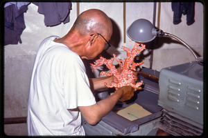 Arts and crafts factory: worker carving coral