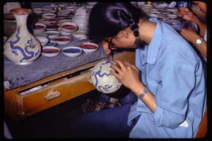 Arts and crafts factory: woman painting ceramics vases with dragon design