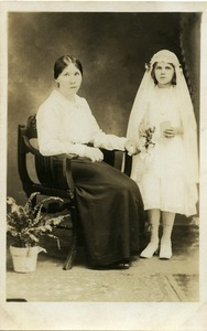 Mother and daughter, Eleanora Sek, at first communion, possibly Easthampton, Mass: full-length studio portrait of mother seated next to daughter