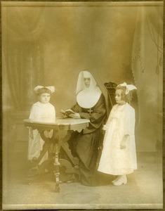 Girls instructed by a nun, possibly Easthampton, Mass.: full-length studio portrait with nun seated at a table, reading, possibly for first communion