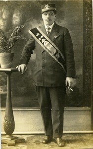 "Member of ""Jolly Get Together"" (Southampton, Mass.), wearing regalia of St. Stanislaw Kostka Brotherhood: full length studio portrait with hand on plant stand"