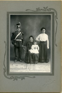 Polish American family portrait: studio portrait with mother and infant seated, man in military uniform with sword on shoulder