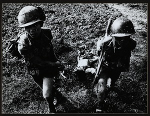 Two ARVN troops drag Viet Cong corpse