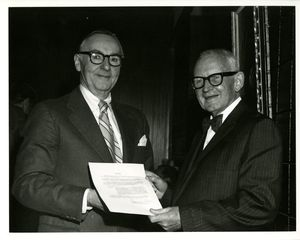 Suffolk University President Thomas A. Fulham (1970-1980) presents a resolution to Professor John O'Brien at O'Brien's retirement party