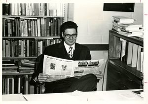 Suffolk University Dean Donald Grunewald (CAS), seated and holding a copy of Suffolk Journal