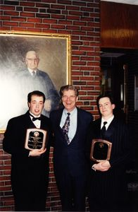 Suffolk University Athletics Director James E. Nelson poses with two students and their awards at the Student Government Awards ceremony