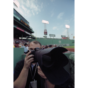 Adam Hunger taking a photograph at a Boston Red Sox game