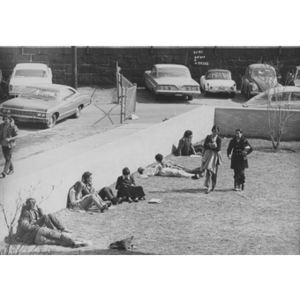Students lounge on grass and against a wall