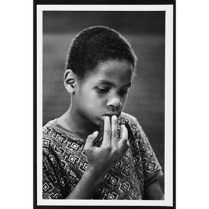 An African American boy from the Boys' Clubs of Boston looking down with his fingers on his lip