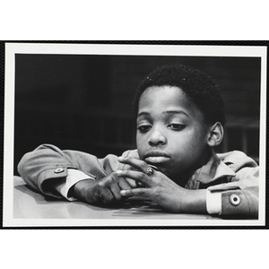 An African American boy from the Boys' Clubs of Boston sitting with his arms on the table