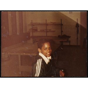 An African American boy smiles for the camera during a class at the Boys and Girls Club