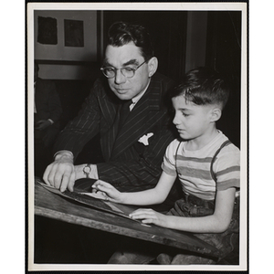 Art Committee member Gardner Cox helps a boy with a drawing at the Boys' Clubs of Boston