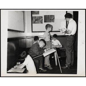 An art instructor and a boy stand together looking at a drawing while four others work on their projects at the Charlestown Boys' Club