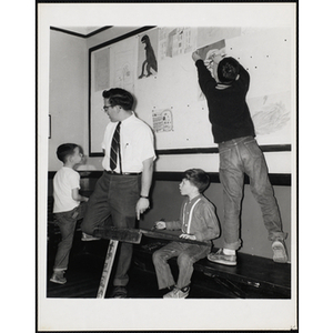 An art instructor and his three students from the Charlestown Boys' Club, one of them pinning up his painting on a board