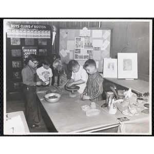 """An art instructor and four boys work on clay projects in the """"Boys' Clubs of Boston booth at Do-It-Yourself Show at Mechanics Building, Boston Nov. 25, 1957"""""""