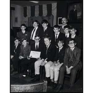Adult Advisor James Munn and twelve boys from the Keystone Club of the Boys' Clubs of Boston posing with a certificate