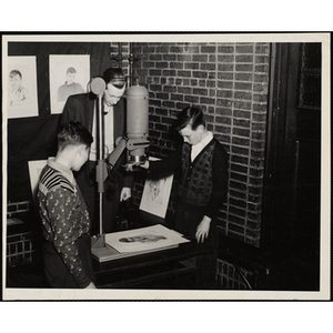 A boy using an enlarger while a man and another boy look on at a photographic laboratory