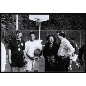 President and CEO of the Boys and Girls Club of Boston Frances K. Moseley (third from left) poses with three attendees of a Chelsea Housing Authority Basketball League game