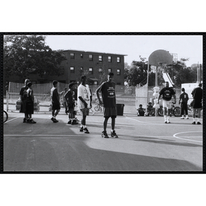 Players perform warm-up drills during a Chelsea Housing Authority Basketball League game
