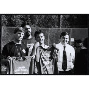 """Men hold up """"Chelsea Housing Authority Basketball League 1993 / Boys and Girls Club"""" t-shirts at a game"""