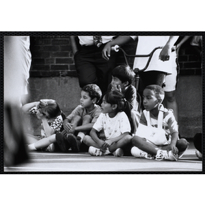 Children sit courtside and watch a Chelsea Housing Authority Basketball League game