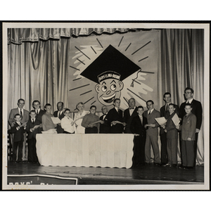 Adults and boys pose with certificates on a stage during a Father and Son's Banquet