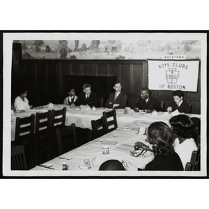 Adults and boys sit at adjoining tables during a Mothers' Club event