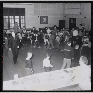 Adults and Children attend a Cake Walk sponsored by the Mothers' Club