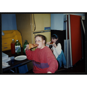 Boy and girl eating pizza slices at a table
