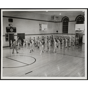 About fifty boys doing warm-up exercises in the South Boston Boys' Club gymnasium