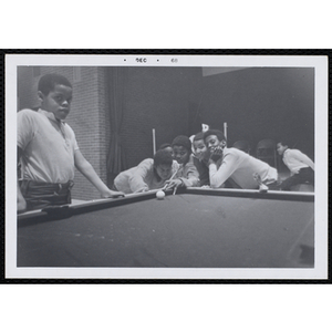 A Boy prepares to take his shot at a pool table