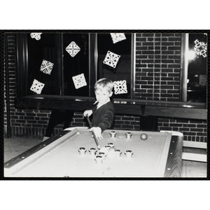 A Boy playing a game of bumper pool