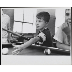 A boy reaches for the cue ball at a pool table