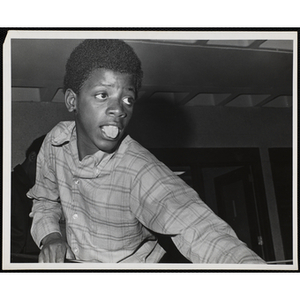 A boy sticks out his tongue while playing a game of pool