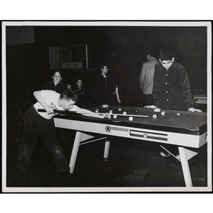 A boy prepares to take his shot in a game of pool