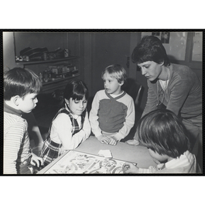 Children play the Candyland board game as a woman looks on