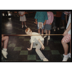 A Boy dancing under a pool cue being used as a limbo stick